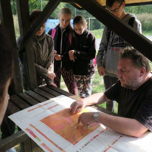 """Mgr. Marek Chvátal nám nejprve u rozložené geologické mapy povyprávěl o geologickém vývoji okolí Světlé nad Sázavou a o """"evolučních"""" peripetiích řečiště řeky Sázavy."""