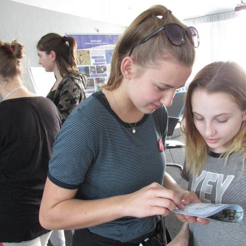 Žáci ze ZŠ Komenského u panelu věnovanému nebezpečným skleněným plochám nahlížejí do brožury ČSO Ptáci a sklo.