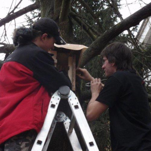 """Poslední únorové odpoledne se pak neslo v rámci hesla: """"Vzhůru na stromy"""". Nejdříve jsme ještě posílili ochranu střechy vrstvou linolea (díky Martino Pacholíková za nezištnou pomoc) a připravili jsme si závěsný aparát tak, aby vlastní zavěšení na stromy neznamenalo žádné poškození stromu a zároveň bylo pro naše zavěšovatele co nejpohodlnější a nejbezpečnější."""