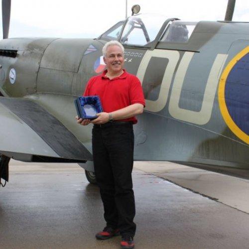 Dan Griffith s cenou vyrobenou skláři naší Akademie před Spitfirem v barvách Otto Smika